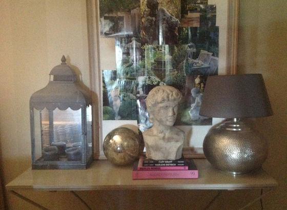 Console con busto, lampada, lanterna e una cornice con varie immagini