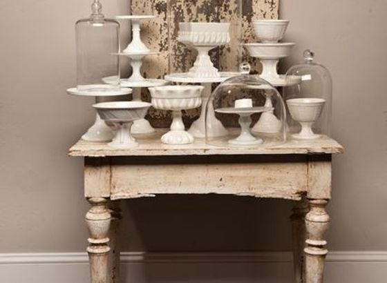 Piccolo tavolo con varie alzate bianche e cupole di vetro